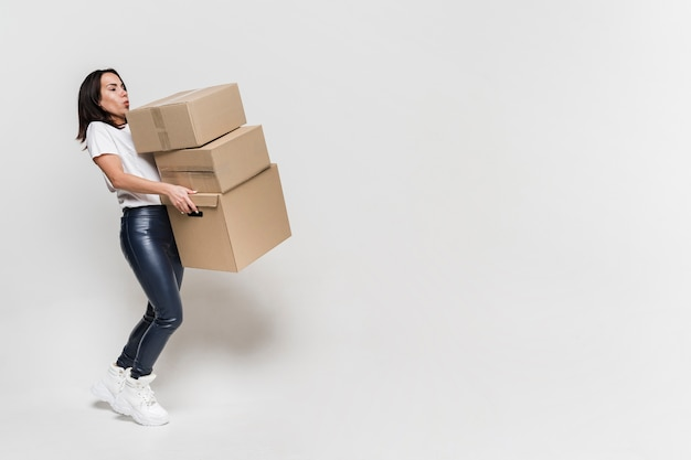 Portrait of young woman carrying cardboard boxes Free Photo
