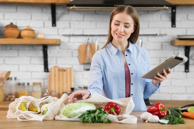 Portrait of young woman checking organic groceries Free Photo
