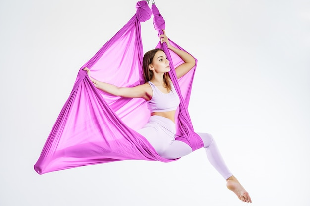 Portrait of a young woman doing anti-gravity yoga. the concept of harmony and tranquility Premium Photo