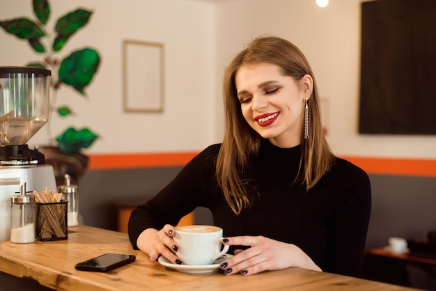 Portrait of young woman drinking coffee in cafe. Premium Photo