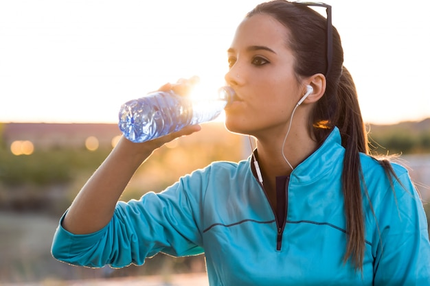 Portrait of young woman drinking water after running. Free Photo