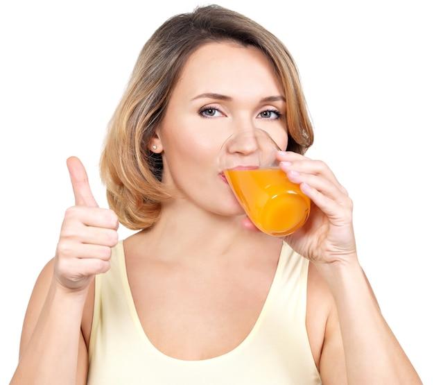Ritratto di una giovane donna beve succo d'arancia isolato su bianco. Foto Gratuite