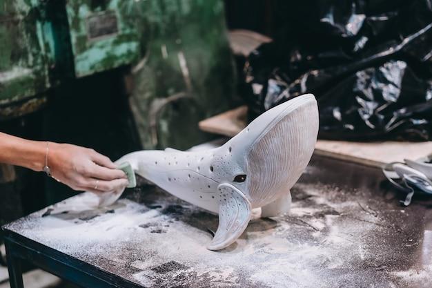 Ritratto di giovane donna che gode del lavoro preferito in officina. il vasaio lavora con cura sulla balena in ceramica Foto Gratuite