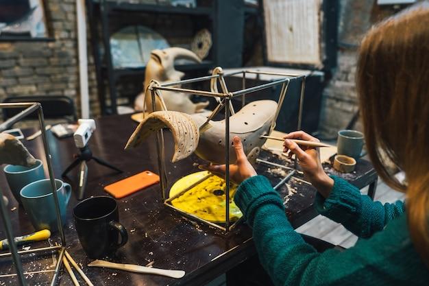 Ritratto di giovane donna che gode del lavoro preferito in officina. potter lavora con cura sulla balena di argilla Foto Gratuite