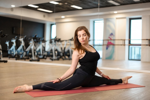 Portrait of young woman in the gym sitting on the splits. fit and wellness lifestyle Premium Photo