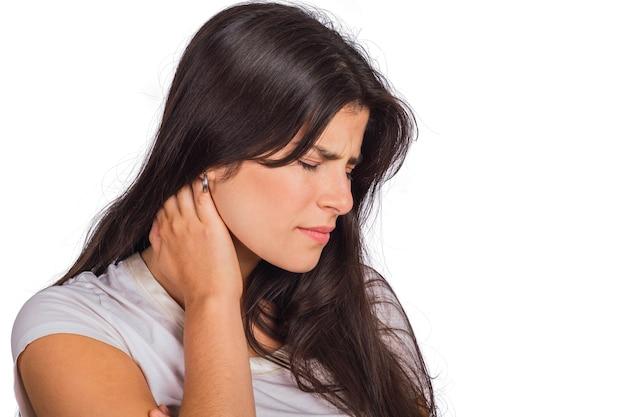 Ritratto di giovane donna che tiene la mano sul collo con dolore al collo in studio. concetto di salute. Foto Gratuite