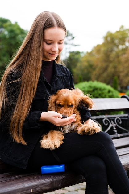 Portrait of young woman holding her dog Free Photo