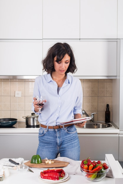 Portrait of a young woman holding wineglass in hand reading the recipe after preparing the food Free Photo
