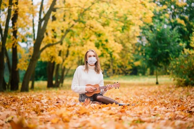 秋の公園でウクレレギターを弾く保護マスクの肖像画の若い女性、ライフスタイル健康旅行の概念 Premium写真