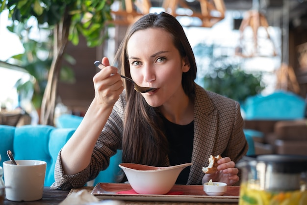 Portrait of a young woman in the interior of the restaurant at the table eating soup with bread, blurred Premium Photo