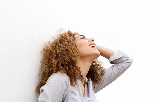 Portrait of young woman laughing with hand in hair Premium Photo