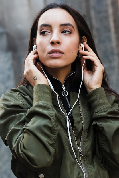 Portrait of a young woman listening music on white earphone Free Photo