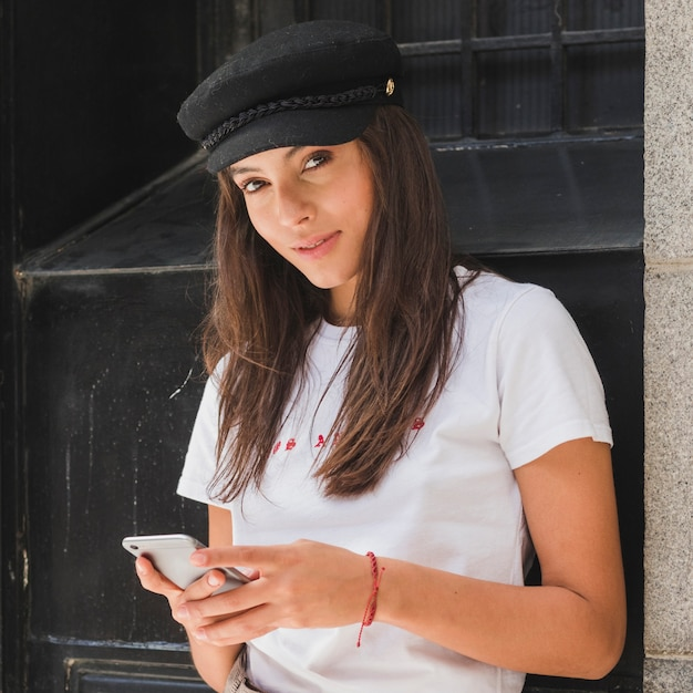 Portrait of a young woman looking at camera using mobile phone Free Photo