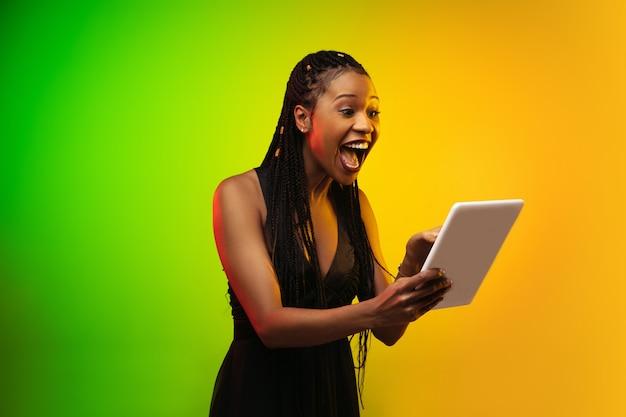 Ritratto di giovane donna in luce al neon su sfondo sfumato. tenendo una tavoletta. Foto Gratuite