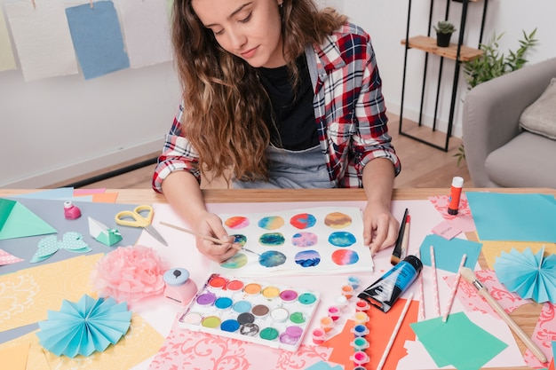 Portrait of young woman painting abstract circle on white paper Free Photo