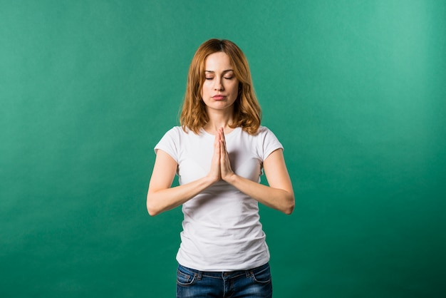 Portrait of a young woman praying against green background Free Photo