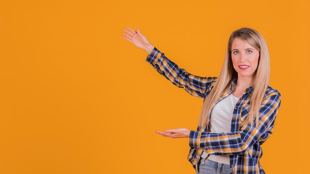 Portrait of a young woman presenting something on an orange backdrop Free Photo