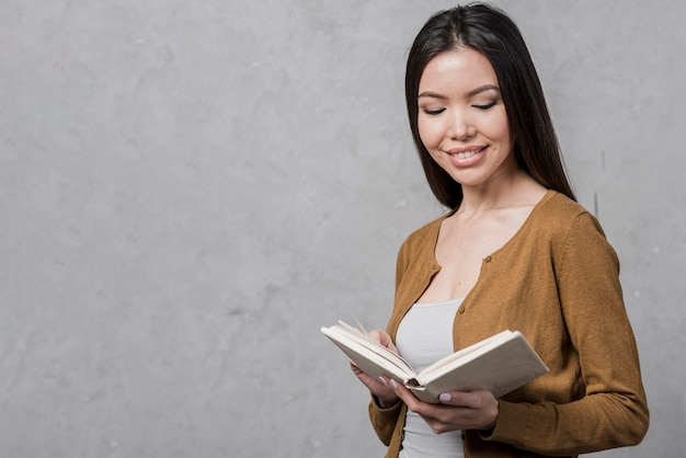 Portrait of young woman reading a book Free Photo