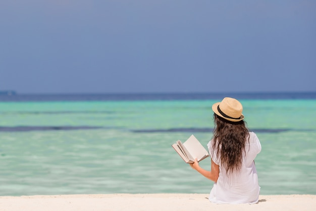 Premium Photo | Portrait of a young woman relaxing on the beach, reading a  book