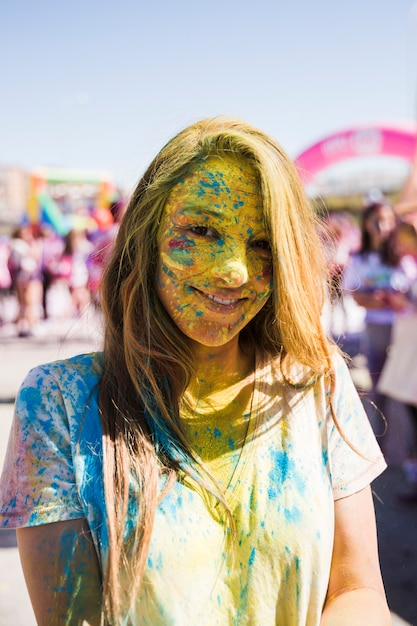 Portrait of a young woman's face covered with holi powder looking at camera Free Photo