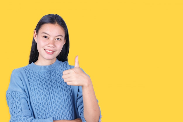 Portrait of young woman show thumb up isolated on yellow background Premium Photo