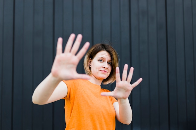 Portrait of a young woman showing stop gesture against black wall Free Photo