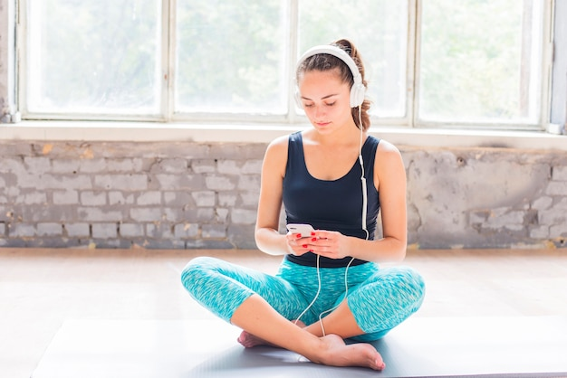 Portrait of a young woman sitting on exercise mat using cellphone Free Photo
