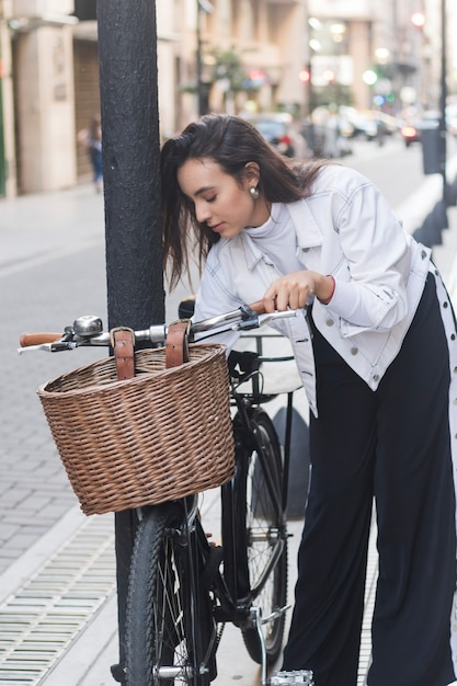 Portrait of young woman standing near the bicycle on street Free Photo