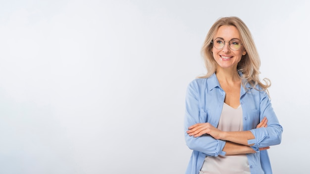 Portrait of young woman standing with her crossed arms against white background Free Photo