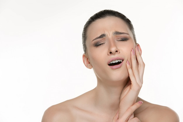 Portrait of young woman suffering from terrible tooth pain Free Photo
