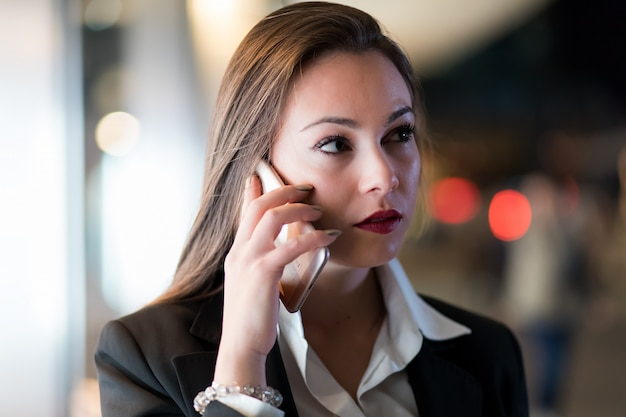 Portrait of a young woman talking on the phone outdoor in the city at late evening Premium Photo