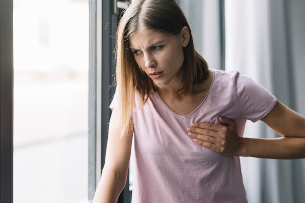 Portrait of a young woman touching her chest in pain Free Photo