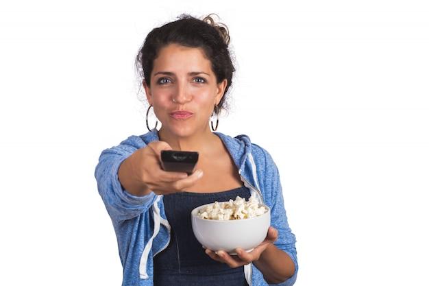 Ritratto di giovane donna che guarda un film e mangia popcorn in studio. Foto Gratuite