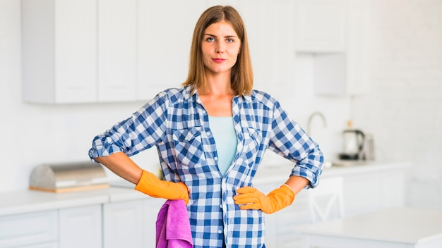 Portrait of young woman wearing hand gloves holding pink napkin Free Photo