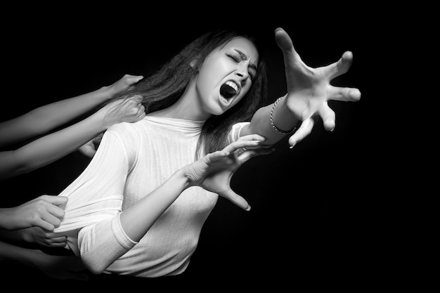 A portrait of a young woman who, with horror and fear, is trying to escape from the many hands pulling her back and tearing her apart. concept of loneliness, loss, fear. scary and terrible portrait Premium Photo