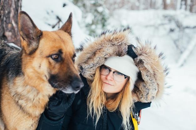 Ritratto di giovane donna in cappotto invernale con il cane Foto Gratuite