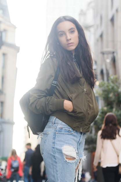 Portrait of a young woman with her hands in pockets looking at camera Free Photo