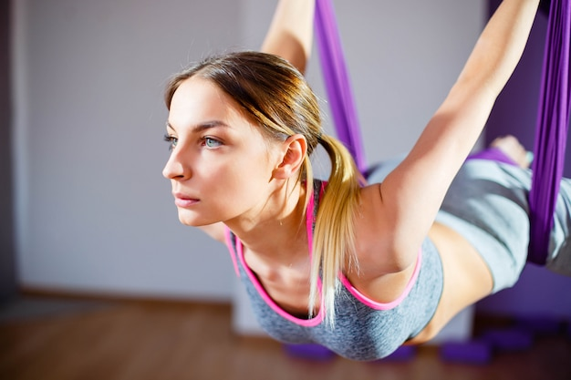 Portrait young women making antigravity yoga. aerial aero fly fitness trainer workout. harmony and serenity concept Premium Photo