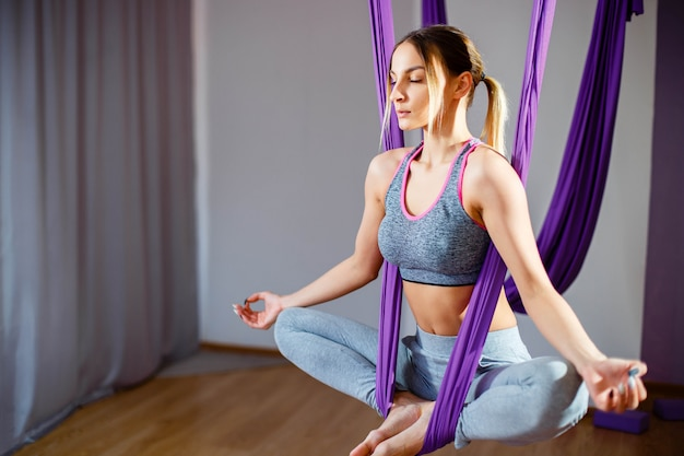 Portrait young women making antigravity yoga exercises. aerial aero fly fitness trainer workout Premium Photo