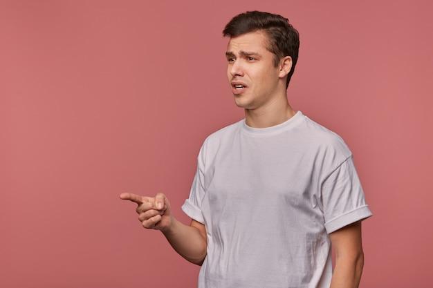Ritratto di giovane ragazzo meravigliato indossa in maglietta vuota, mostra con il dito su qualcosa di incredibile, si leva in piedi sul rosa con spazio di copia, bocca spalancata in un'espressione scioccata. Foto Gratuite