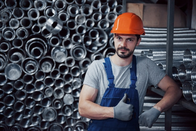 Portrait of a young worker in a hard hat at a large metalworking plant Free Photo