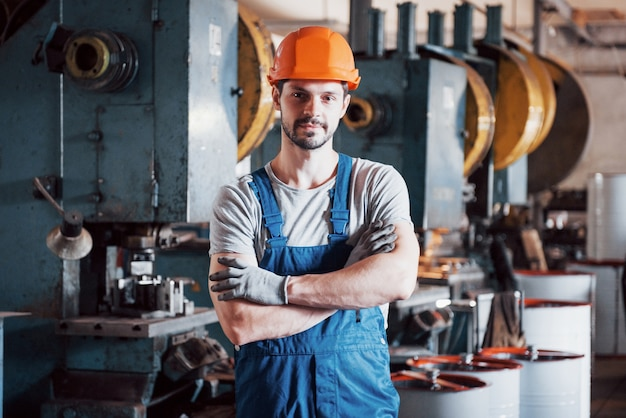 Portrait of a young worker in a hard hat at a large metalworking plant. Free Photo