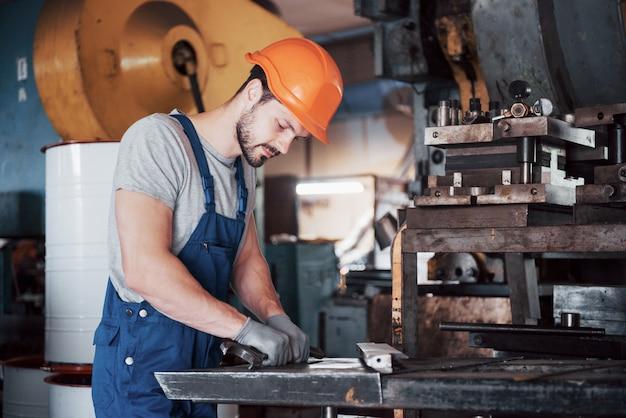 Ritratto di un giovane operaio in un elmetto in una grande fabbrica di riciclaggio dei rifiuti. Foto Gratuite