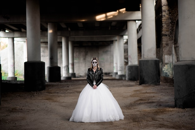Portrait of zombie woman with painted skull face under a bridge. Premium Photo