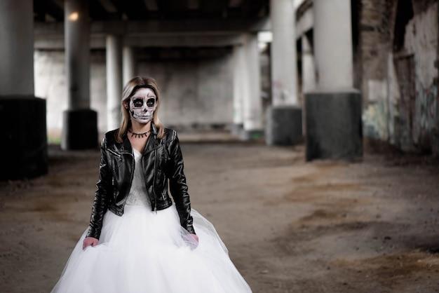 Portrait of zombie woman with painted skull face under a bridge. Premium Photo