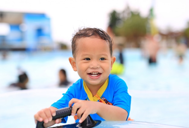 Portraits of happy little asian baby boy smiling having fun at swimming pool outdoor. Premium Photo