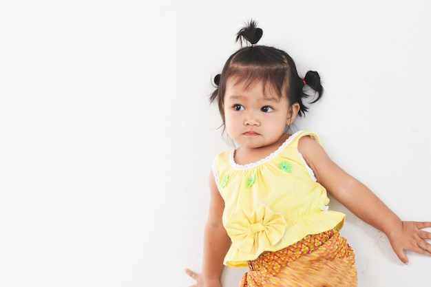 Portriat of cute asian little child girl in thai tradition dress standing in the house Premium Photo