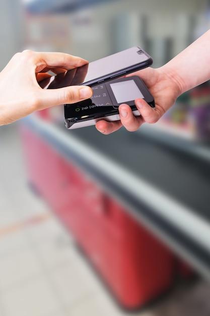 Pos-терминалы и смартфон. на заднем плане - касса супермаркета. банковское оборудование. приобретение. прием банковских кредитных карт. бесконтактная оплата. Premium Фотографии