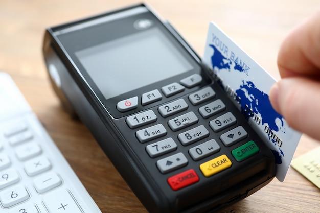 男性の手は、pos端末のクローズアップとクレジットカードを保持します。 Premium写真