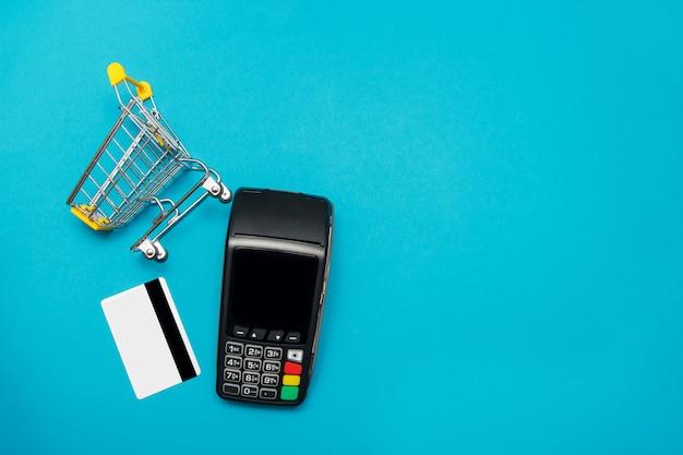 青色の背景にクレジットカードとスーパーマーケットのトロリーとpos決済端末。オンラインショッピングと販売コンセプト。 Premium写真